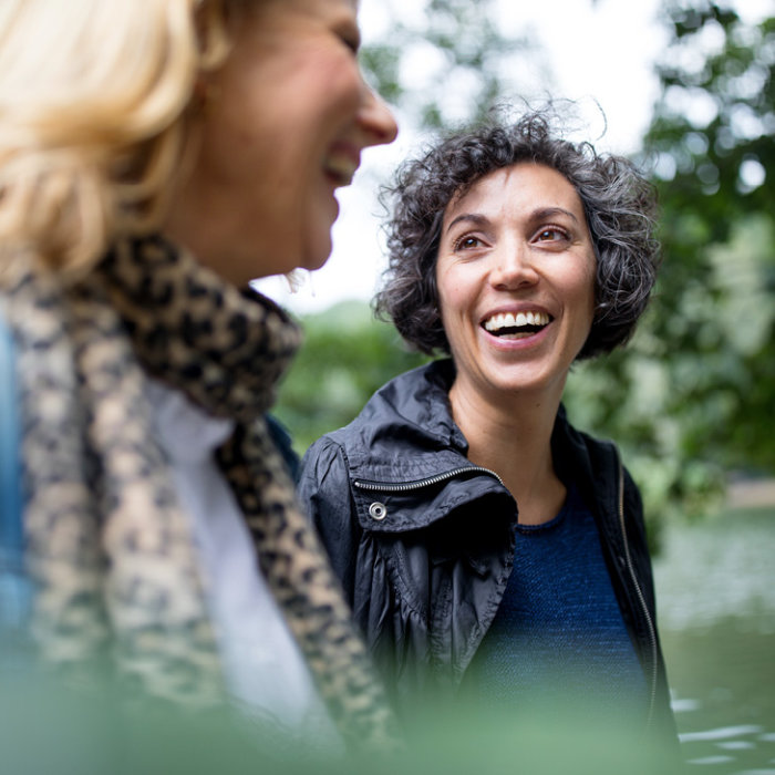 Photo of two woman walking and laughing together