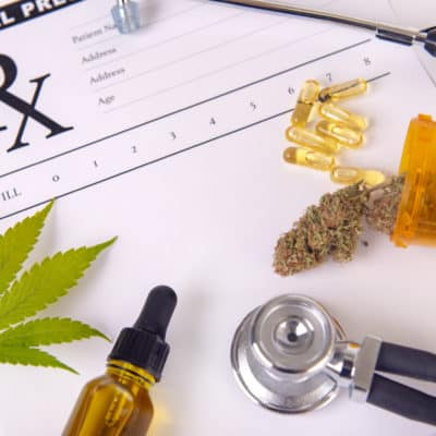 Assorted cannabis products, pills and CBD oil over medical prescription sheet for How to Get a Medical Marijuana Card.